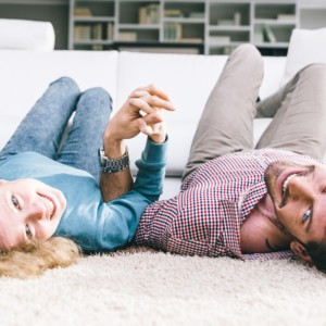 Happy young couple lyind on the Carpet   Flowers Flooring